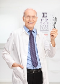 Mature optician holding glasses in his office